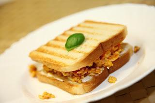 Topli sendvič z umešanimi jajčki, kečapom in kislo smetano