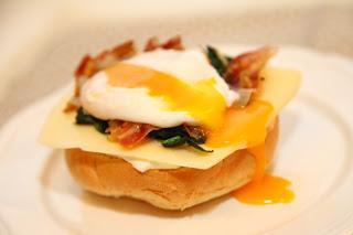 Obložen kruhek s špinačo, panceto, pinjolami in poširanim jajčkom