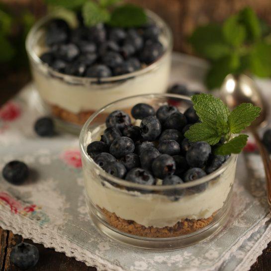 Borovničeve lahke kremne tortice v kozarčku z rikoto, oreščki makadamije in limeto