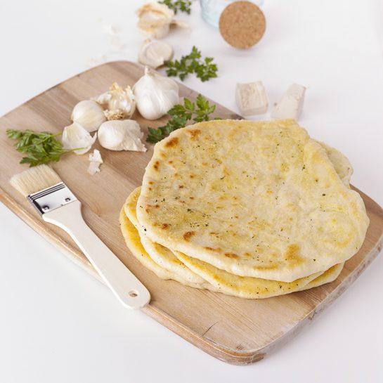 Kvašen tanki kruh naan premazan s česnom in zelišči