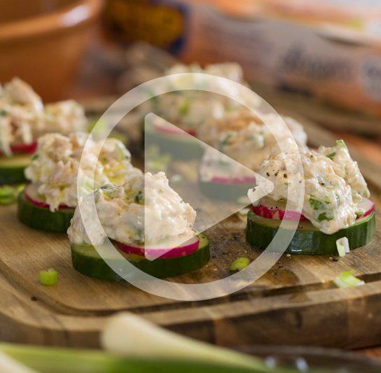 Tunina lahka solata z mlado čebulico in grški jogurtom servirana na kolobarjih sveže kumare