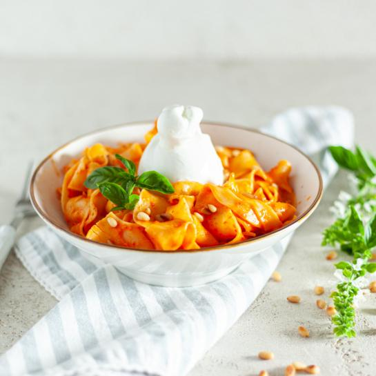 Široki rezanci v paprikini omaki z burrato in pinjolami